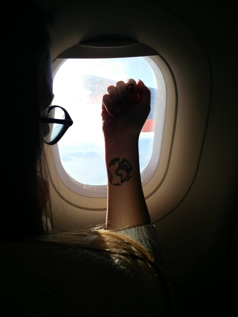 Ragazza al finestrino di un aereo con un tatuaggio sul polso a forma di mondo.